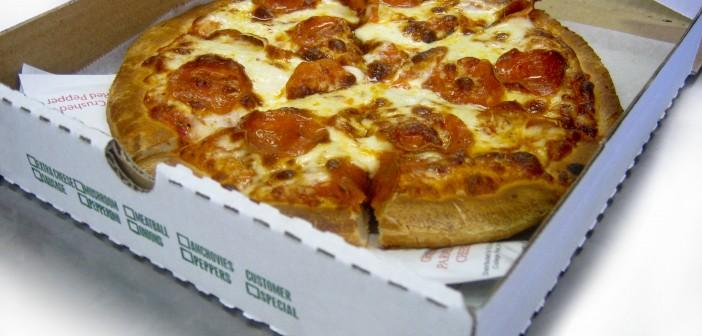 Una pizza nella sua scatola di cartone